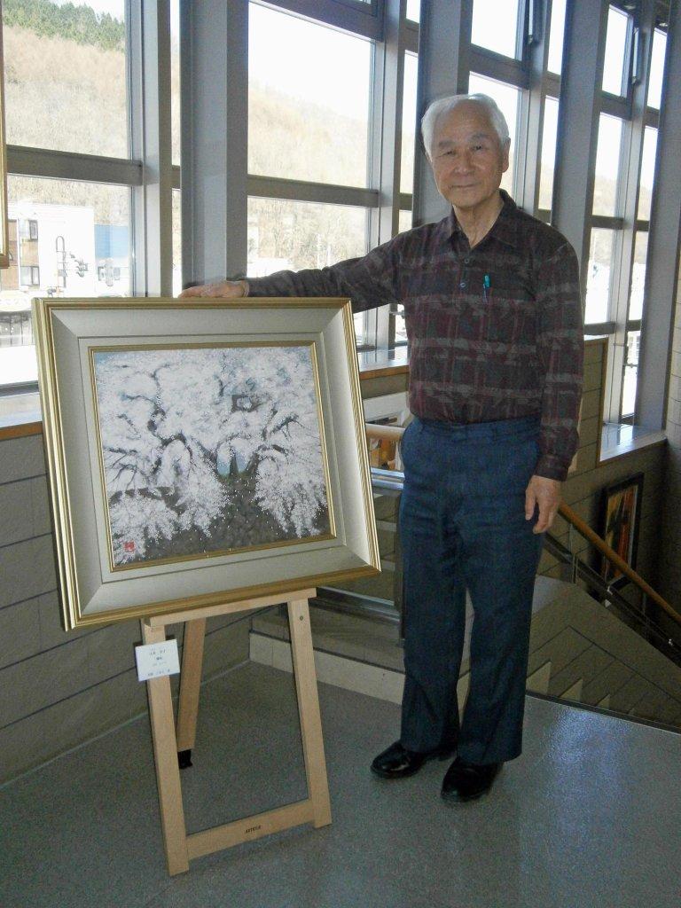 細川昭夫さん。寄贈された絵の前で