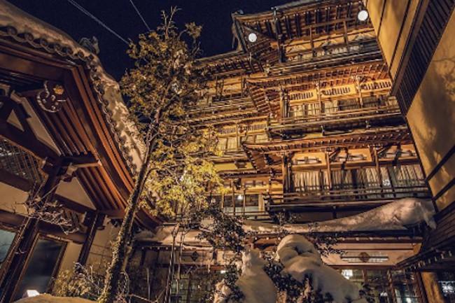 """金具屋は長野県の""""渋温泉""""という、石畳が続く情緒ある雰囲気が漂う場所にあるお宿です。このあたりにはさまざまな温泉や旅館が数多く並んでいます。歴史の宿といわれるように1758年から今に渡り長年経営されており、現在は九代目が継いでいるそうです。外観も非常に素晴らしい見栄えで日本だけにとどまらず、海外からも一目見たいと多くの観光客が訪れます。"""