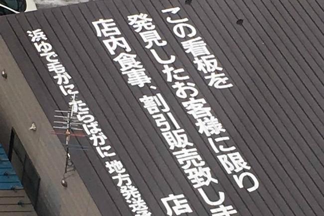 なぜそんな場所に?ビルの上からしか見えない函館の珍看板が話題