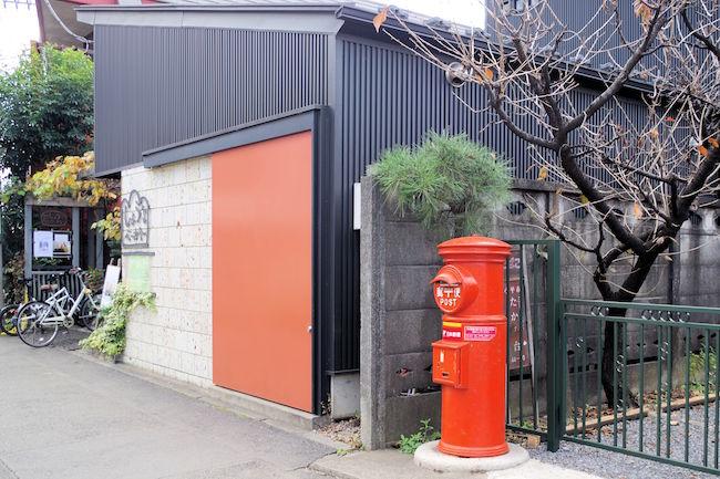ポストのレトロな丸いボディーと、パン屋さんのシックでフラットな赤い扉が対照的で良いですね